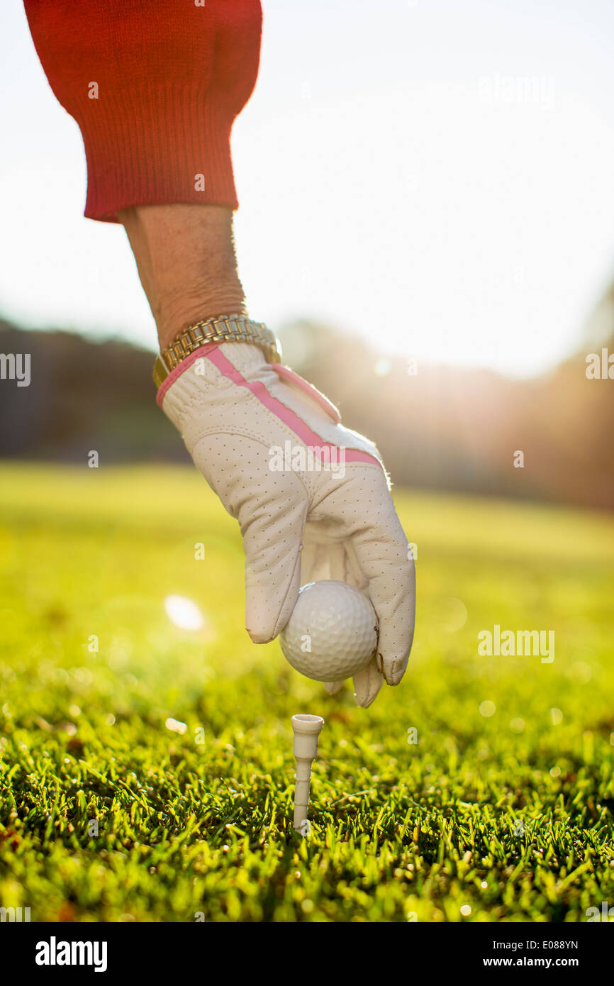 Woman placing golf ball on tee - Stock Image