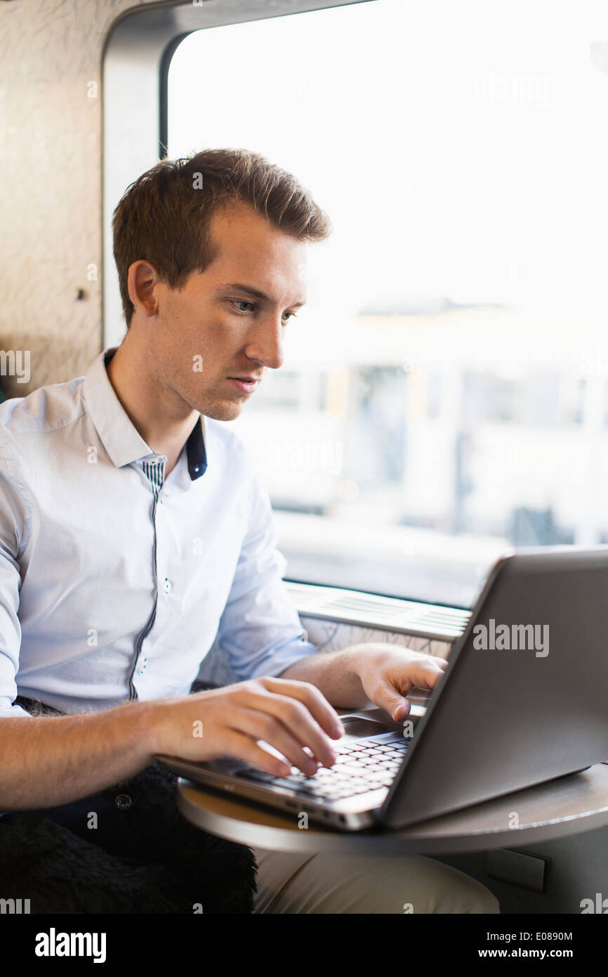 Young businessman using laptop on train - Stock Image