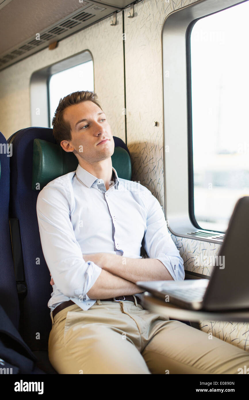 Thoughtful young businessman on train - Stock Image