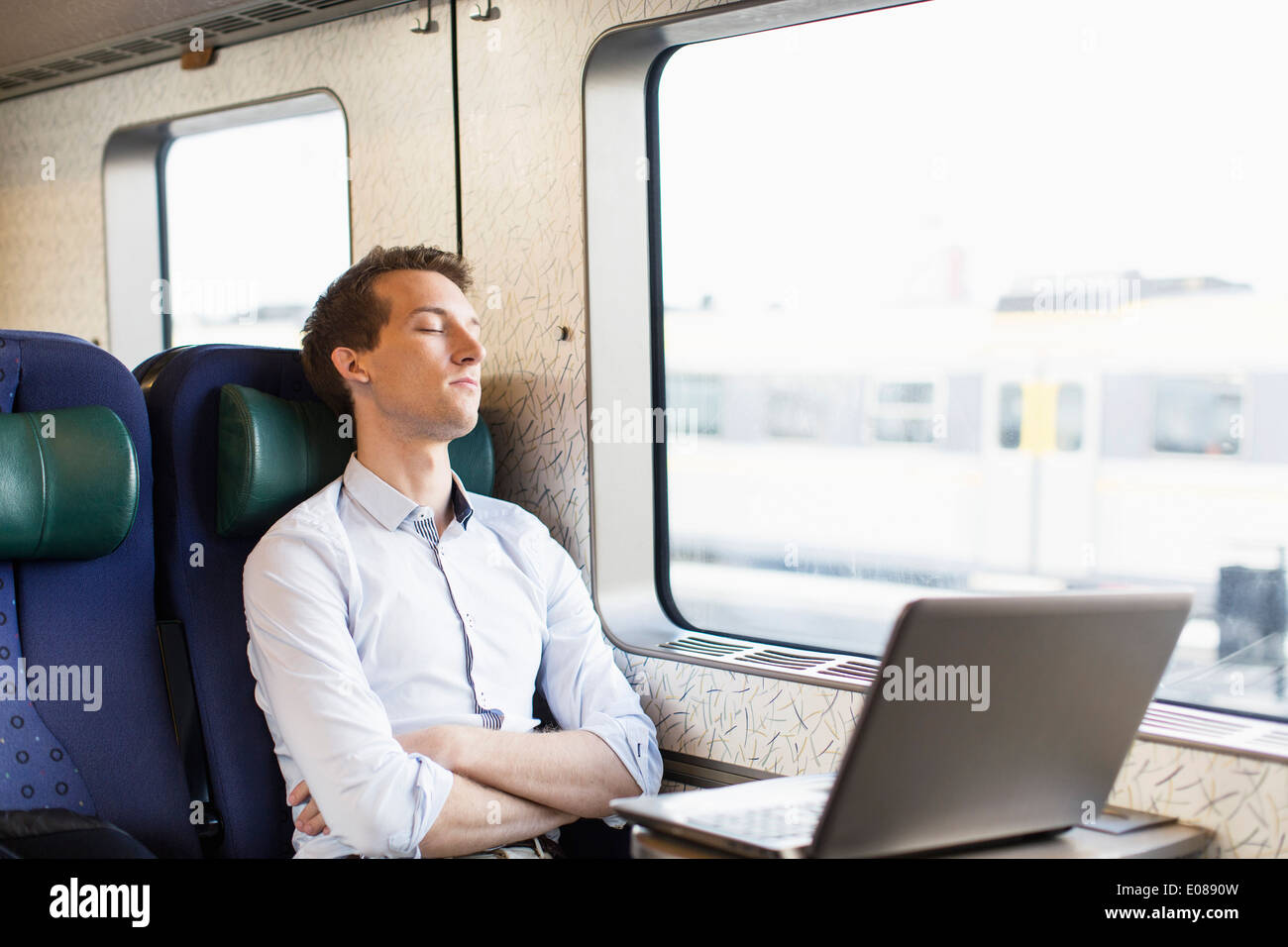 Young businessman sleeping on train - Stock Image