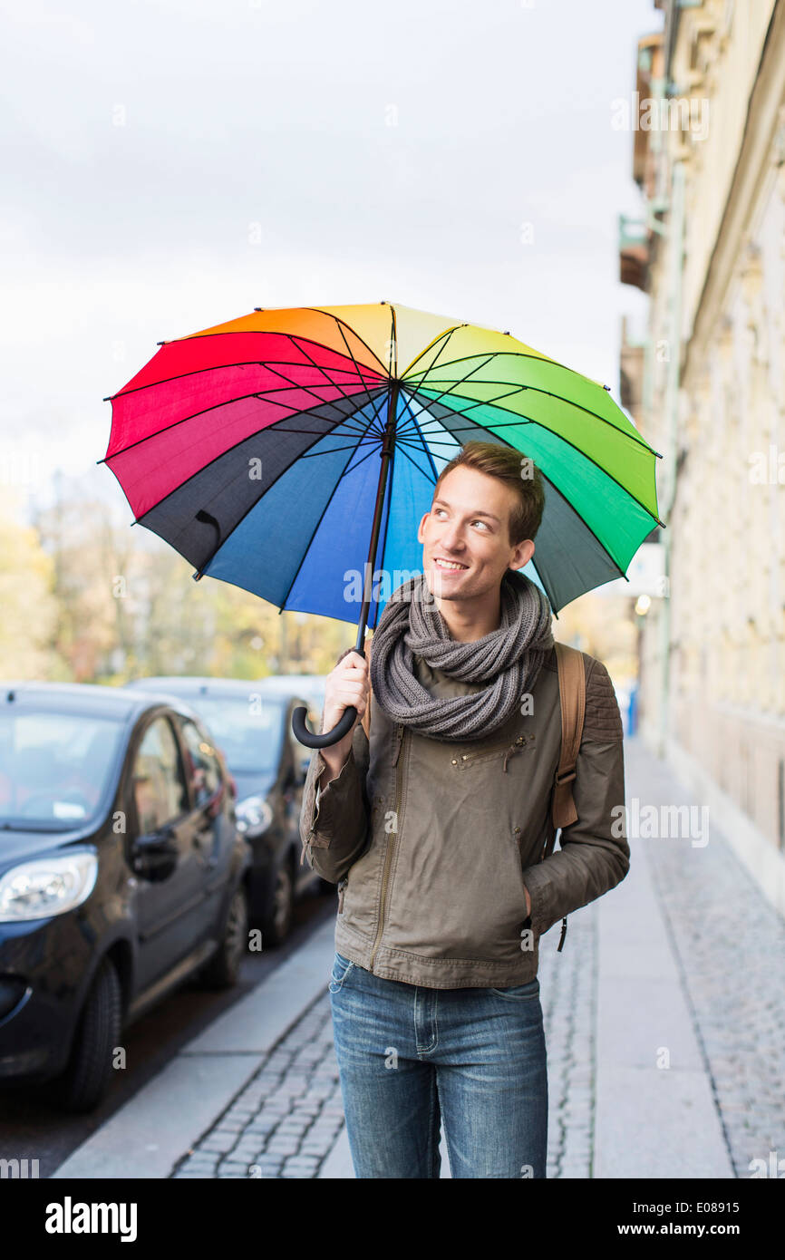 Young businessman with umbrella walking on footpath - Stock Image