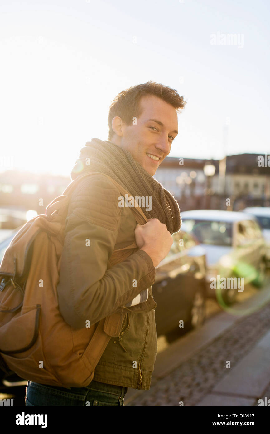 Portrait of young businessman with backpack walking on footpath - Stock Image