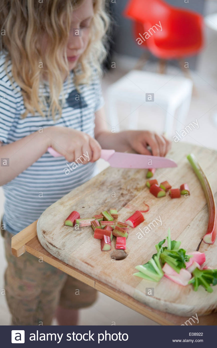 Girl cutting rhubarb into pieces at home - Stock Image