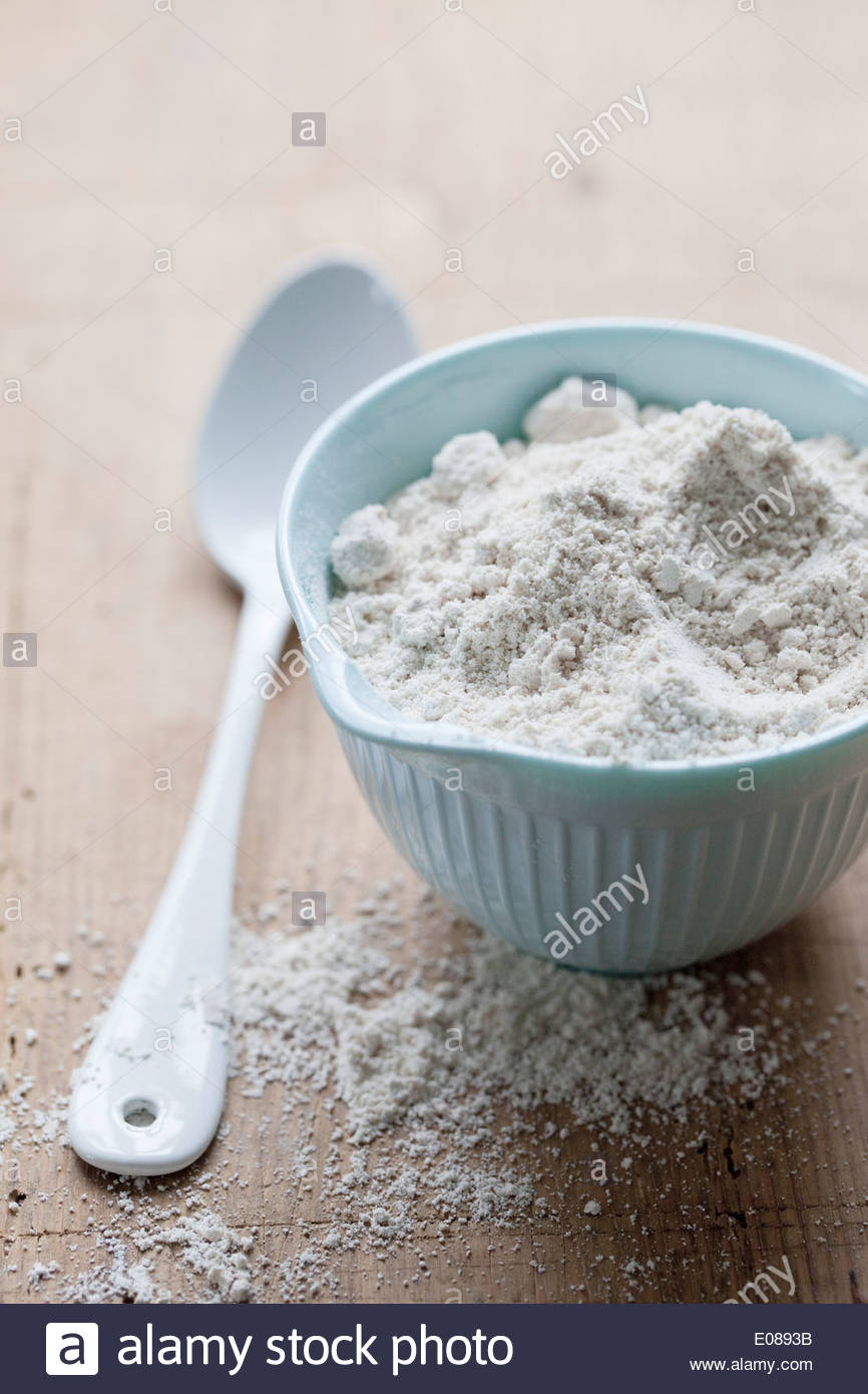 Bowl of flour and spoon on table - Stock Image