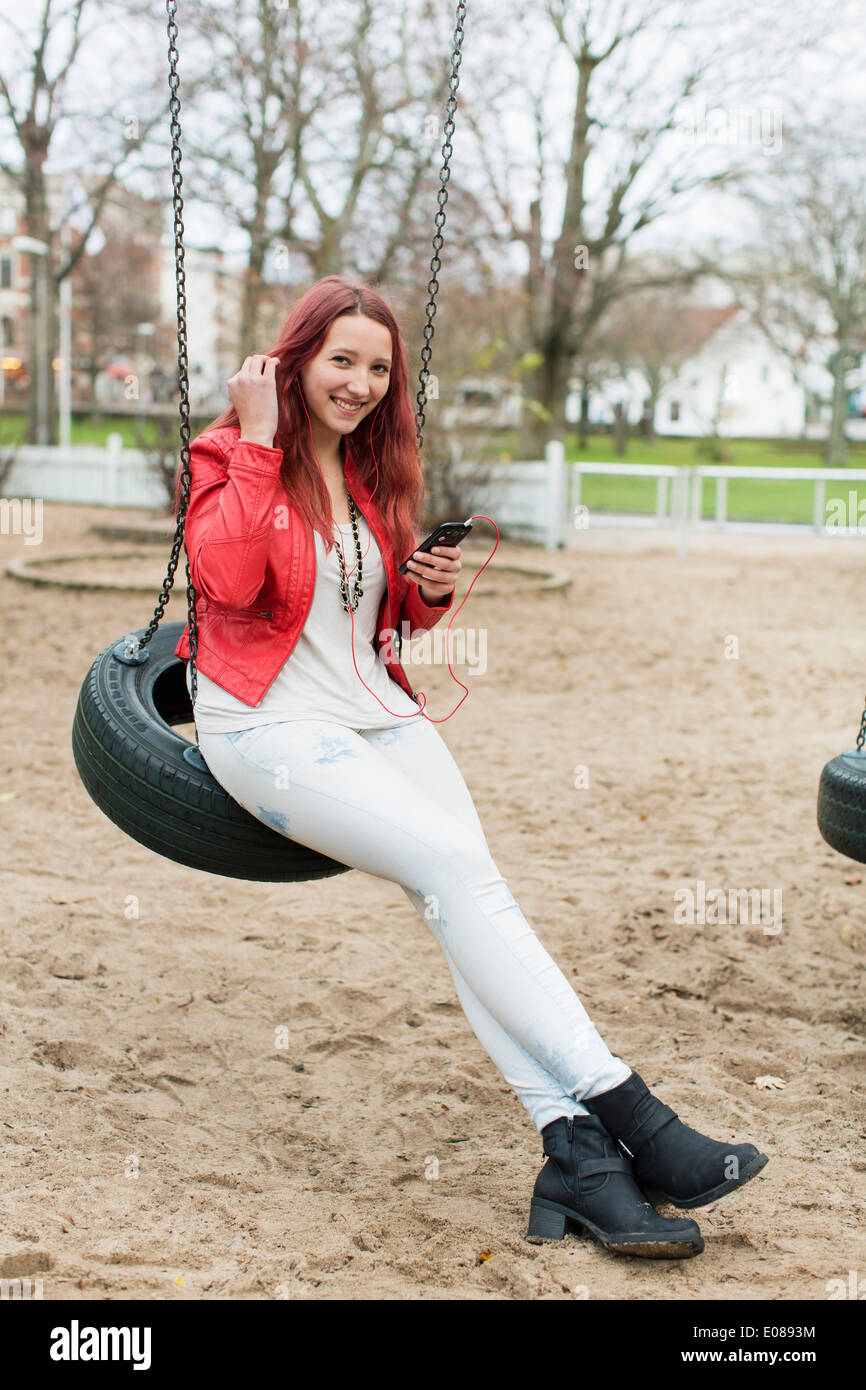 Full length of happy teenage girl enjoying music on tire swing in playground - Stock Image
