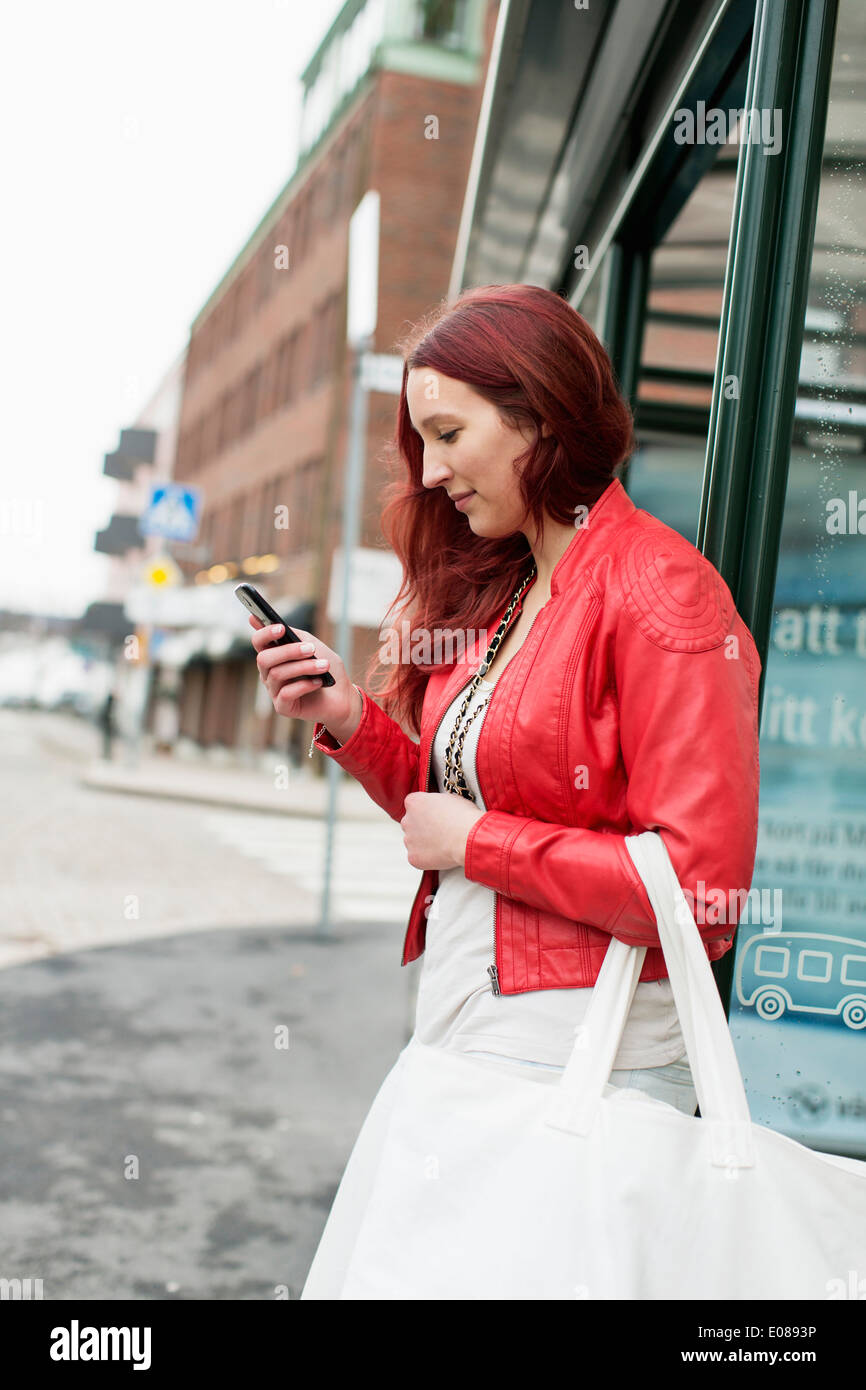 Side view of teenage girl reading text message on city street - Stock Image