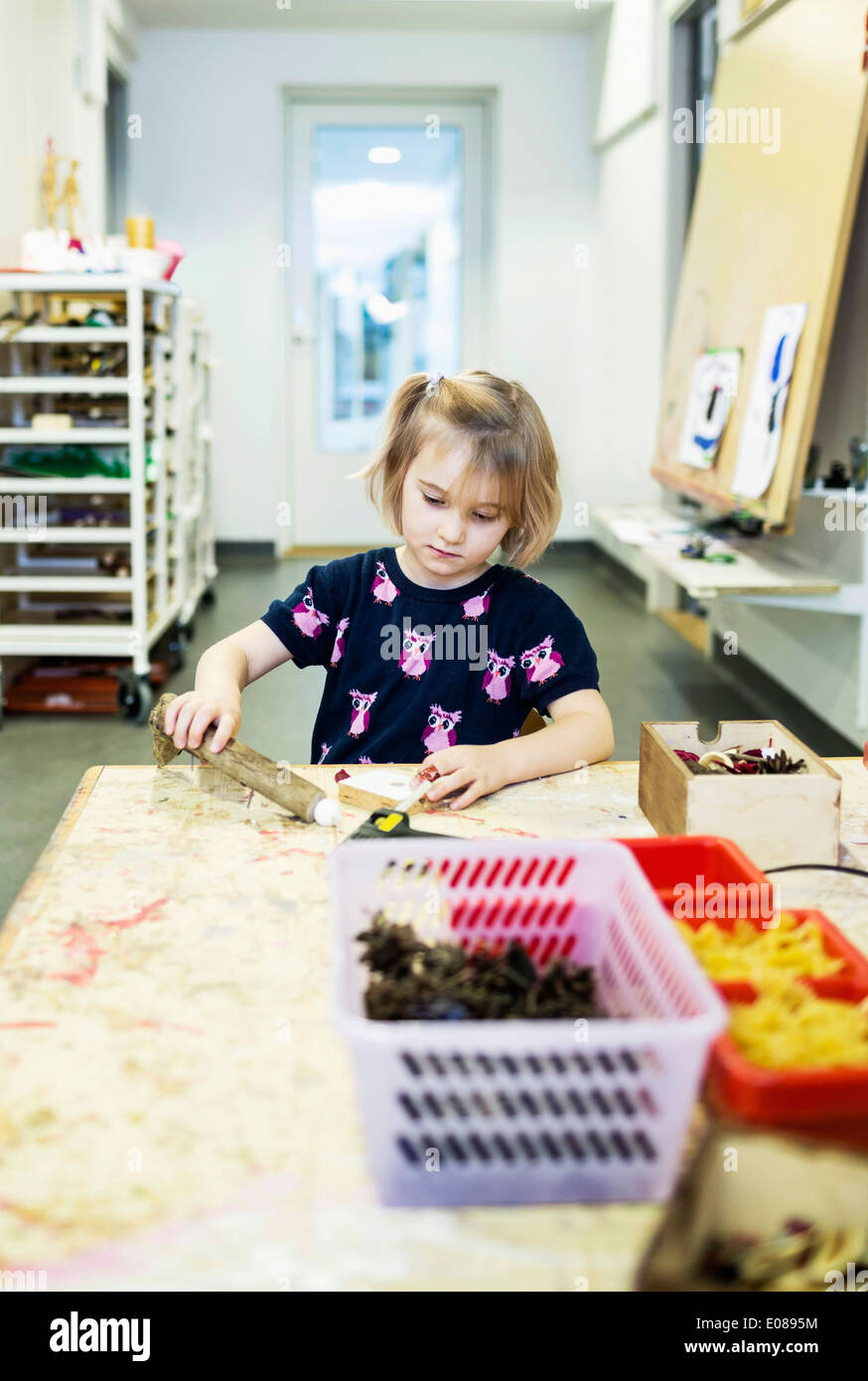 Girl making art product at table in kindergarten - Stock Image