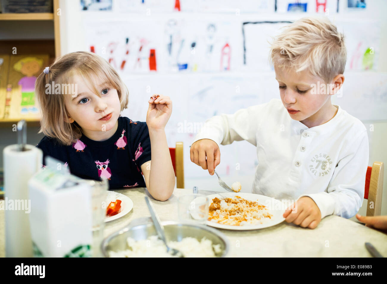 Elementary students having food in kindergarten - Stock Image