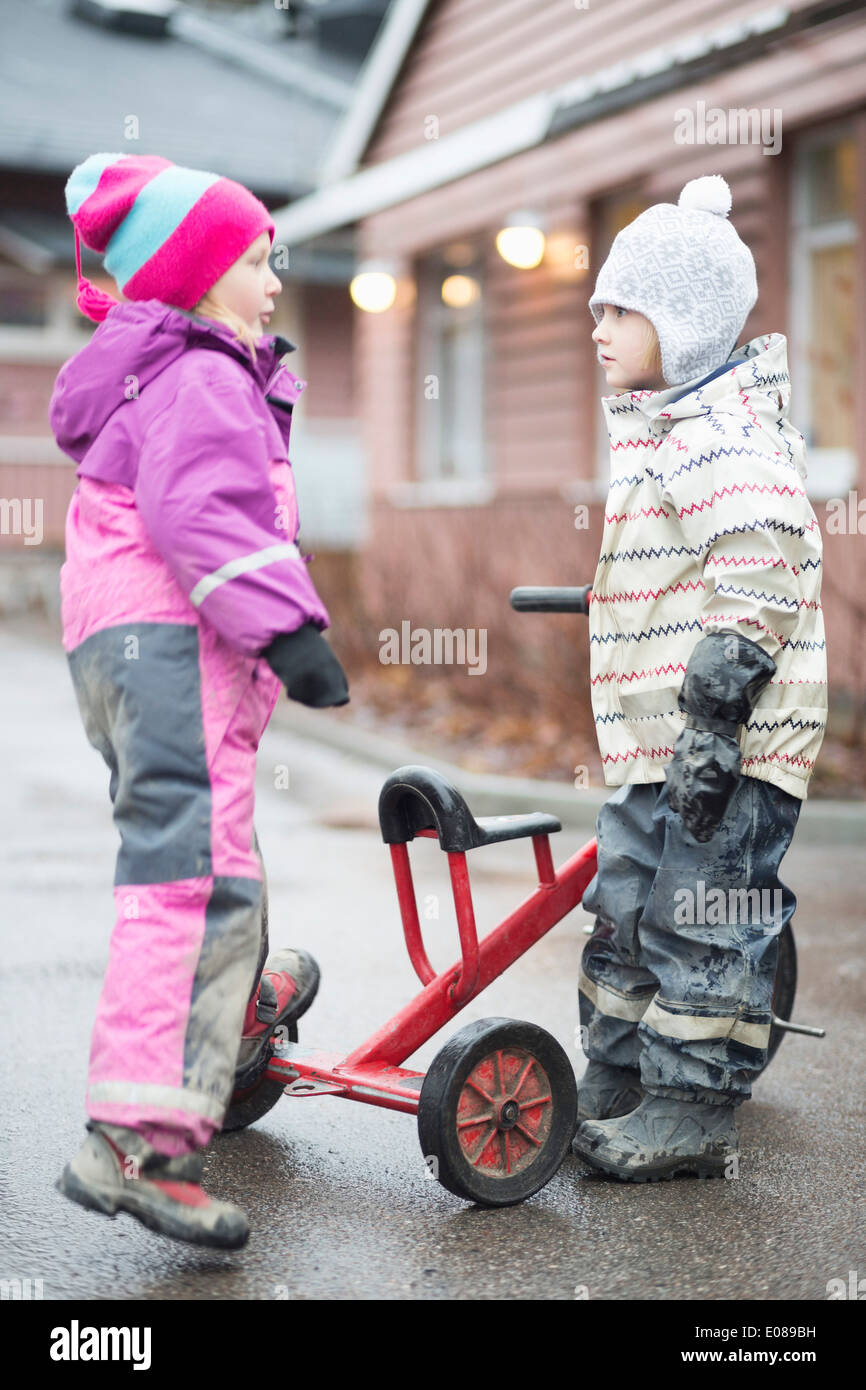 Side view of elementary girls with tricycle standing at yard - Stock Image