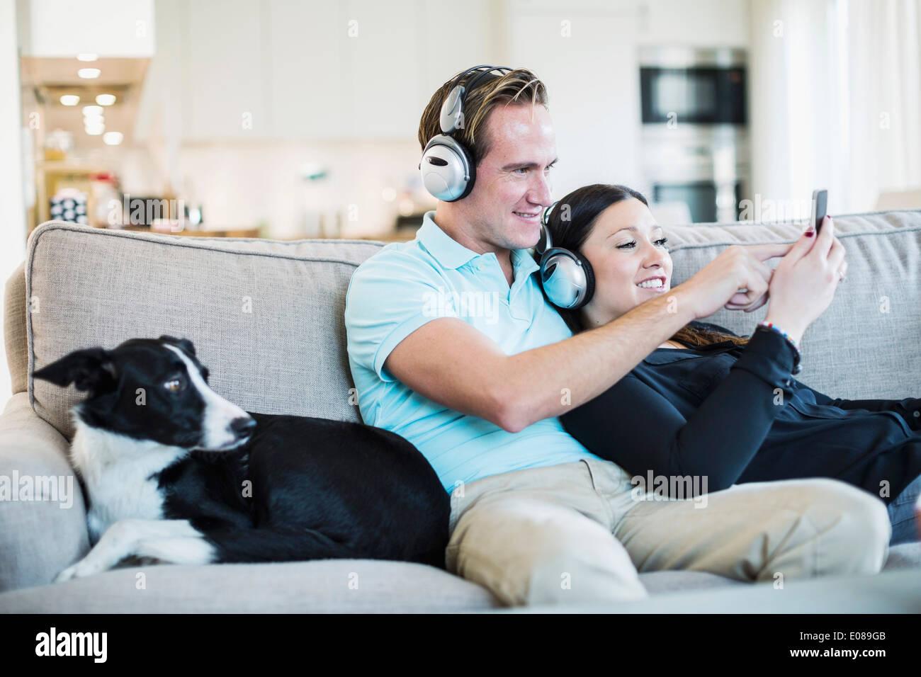 Couple listening to headphones with dog sitting on sofa - Stock Image