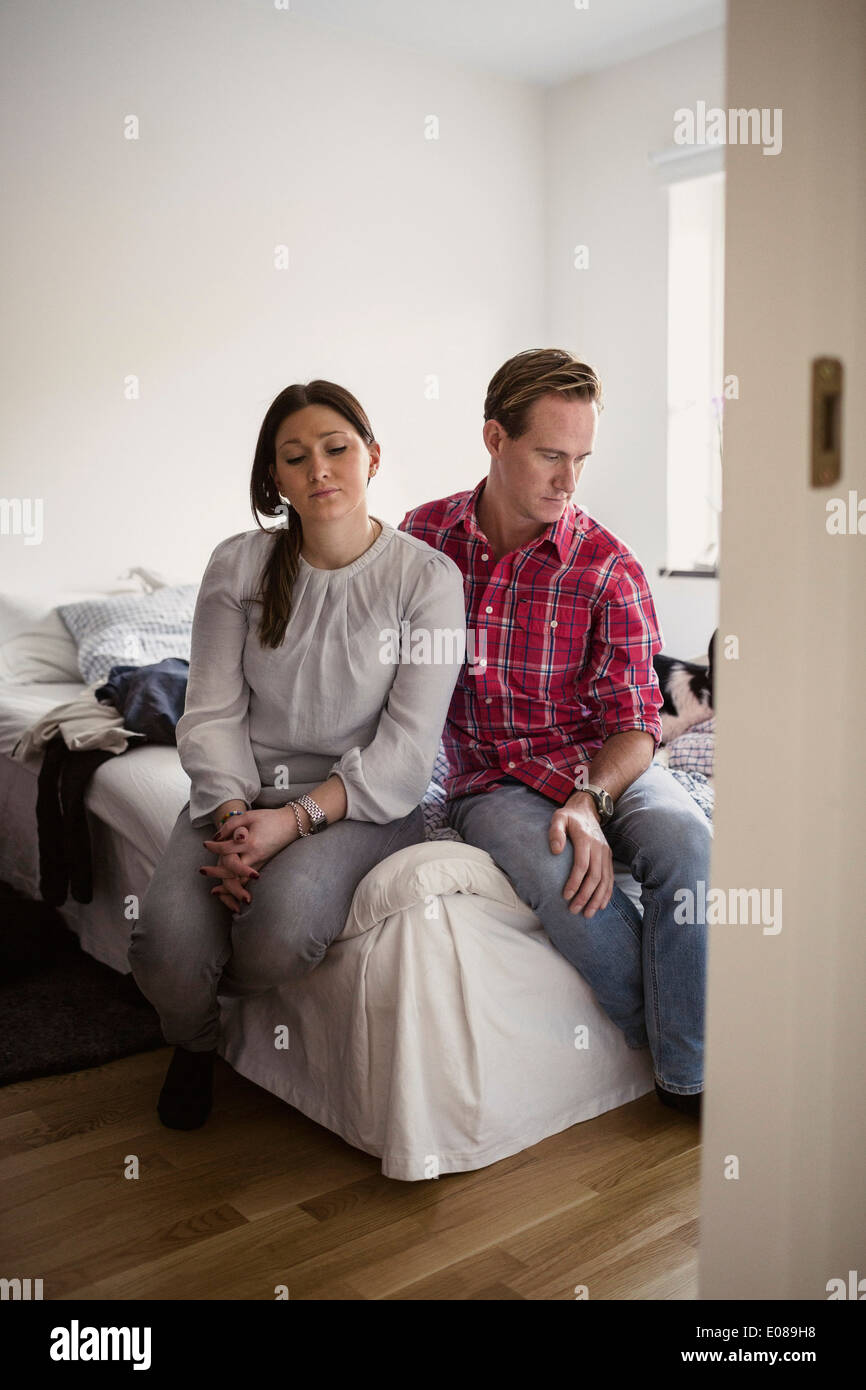 Sad couple sitting on bed at home - Stock Image