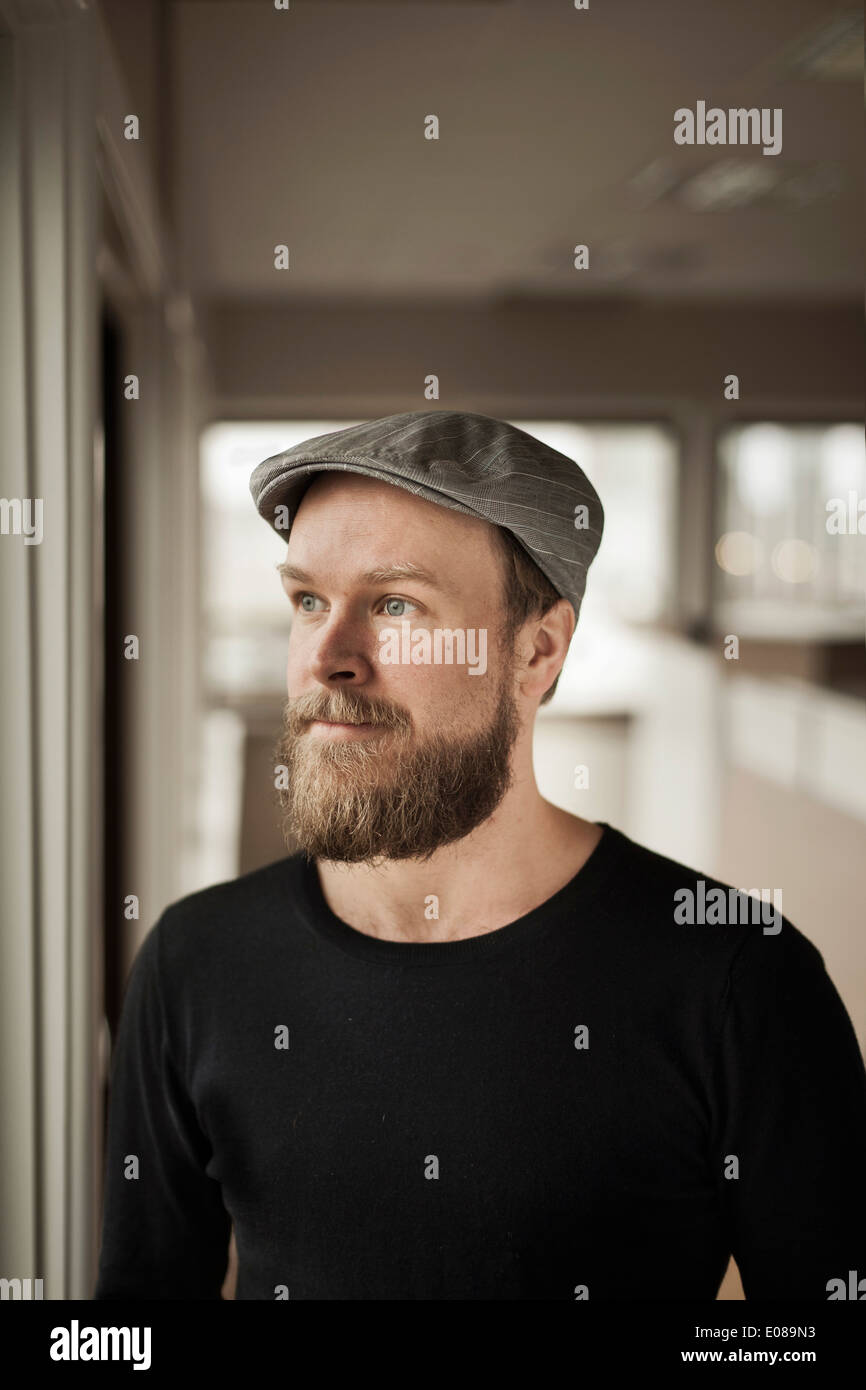 Thoughtful businessman looking away in office - Stock Image
