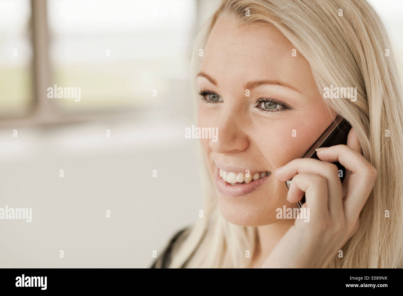 Businesswoman using mobile phone in office - Stock Image