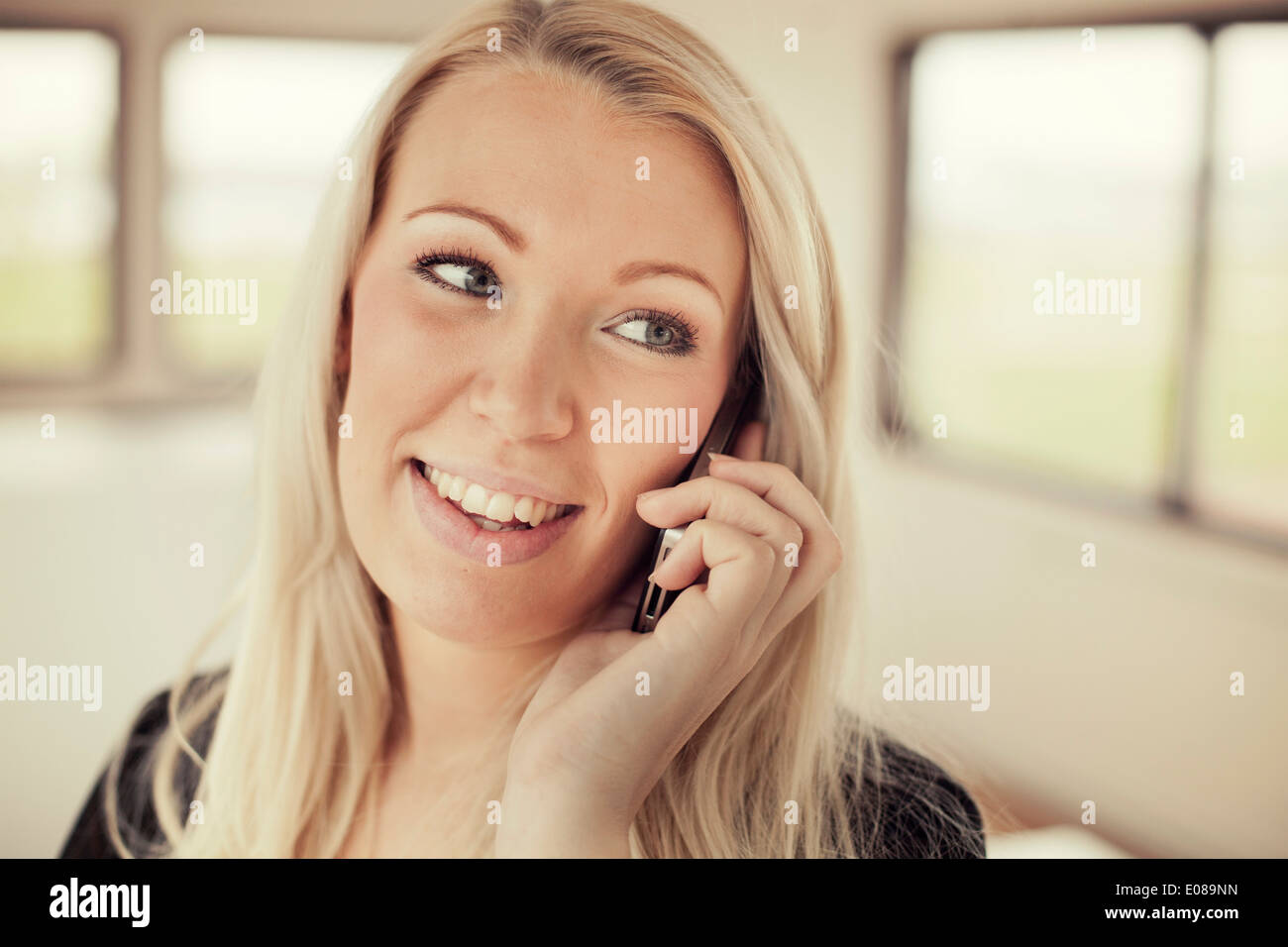 Businesswoman using mobile phone  while looking away in office - Stock Image
