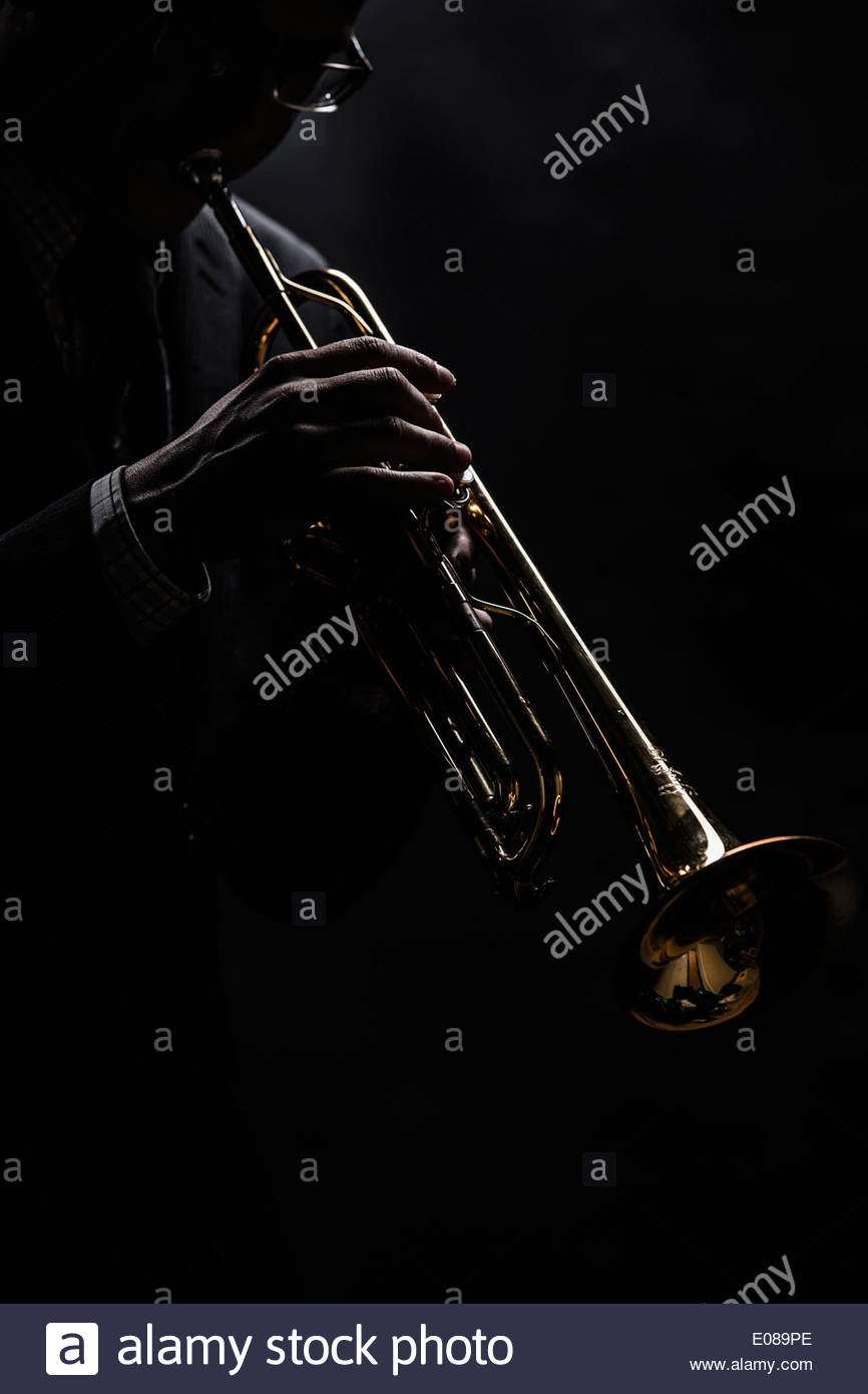 Musician playing trumpet over black background - Stock Image