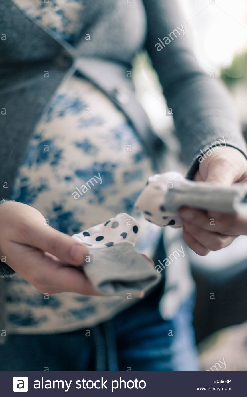 Midsection of pregnant woman holding baby socks in house - Stock Image