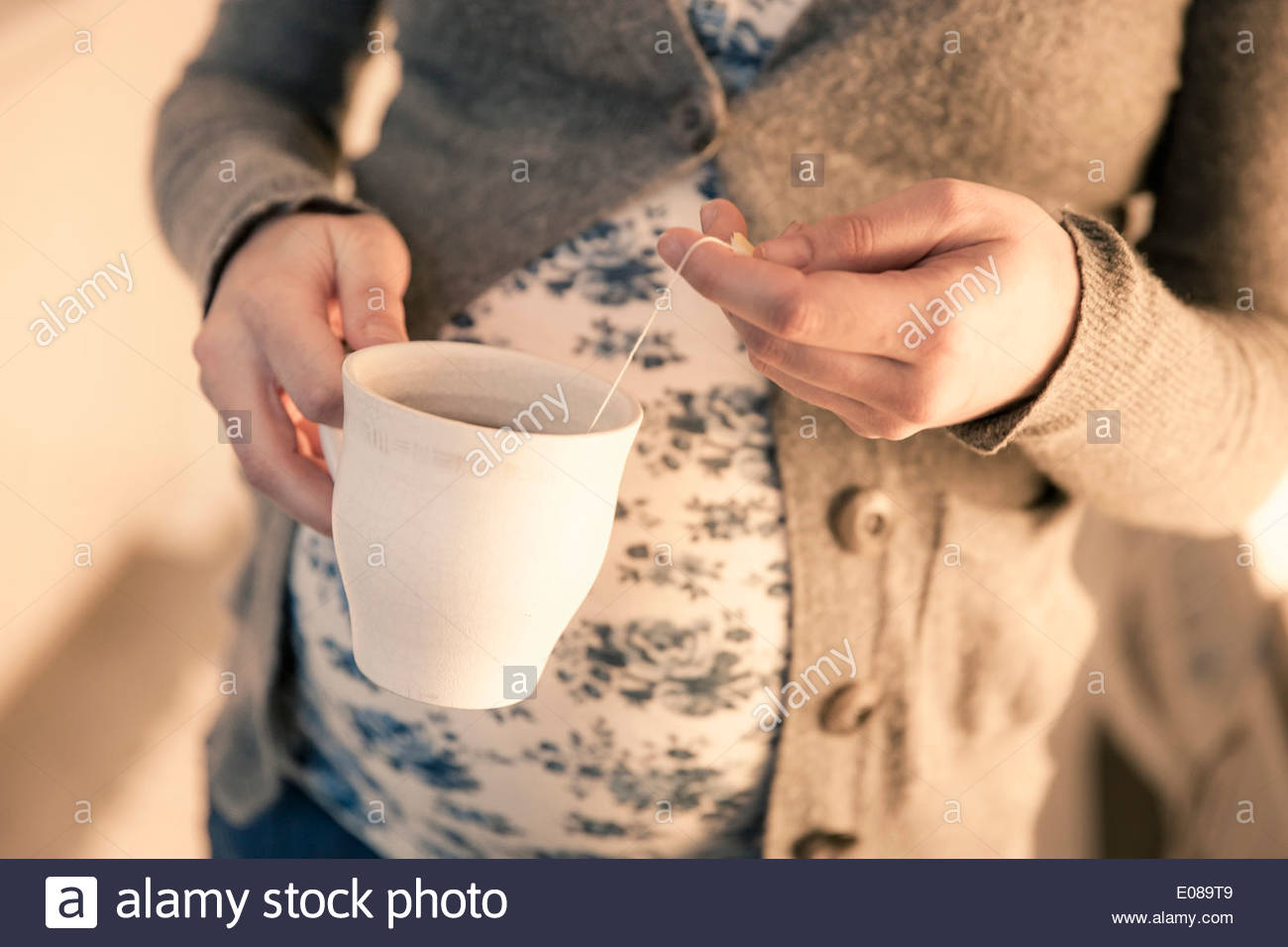 Midsection of pregnant woman dipping teabag into cup - Stock Image