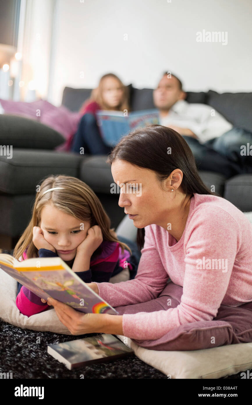 Mother and daughter reading story book on floor with family in background - Stock Image