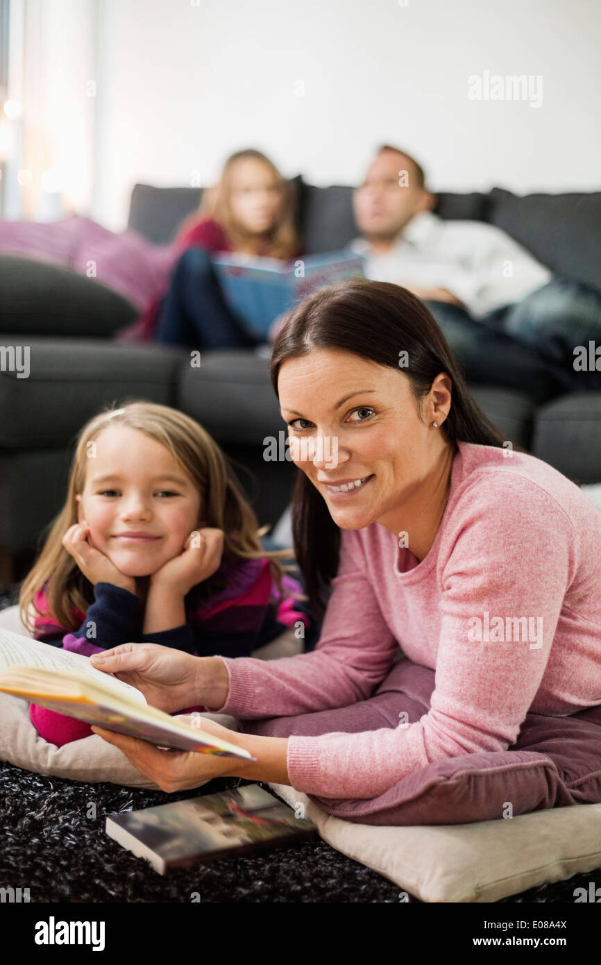 Portrait of happy mother and daughter with story book in living room - Stock Image
