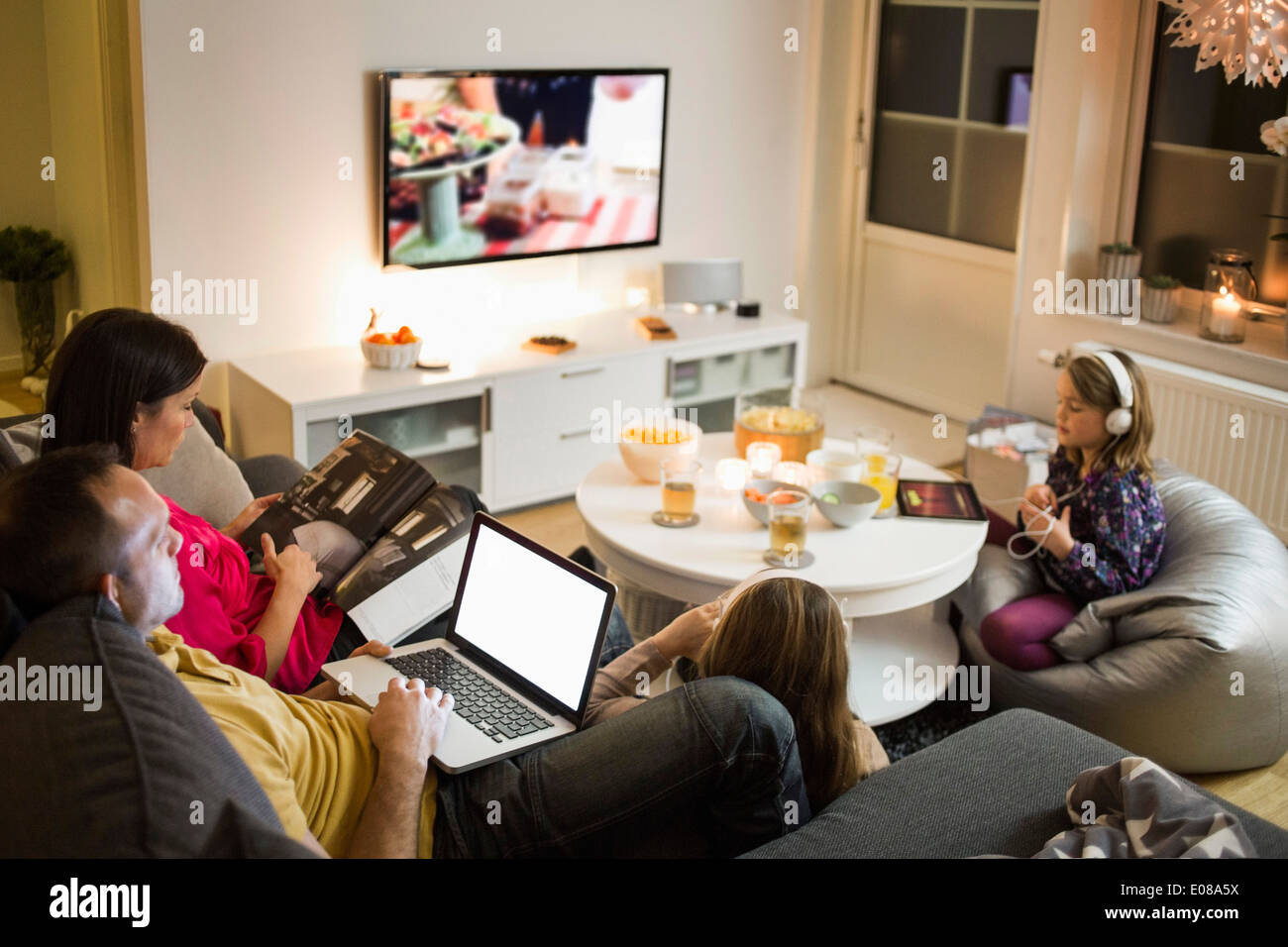 Family using technologies in living room - Stock Image