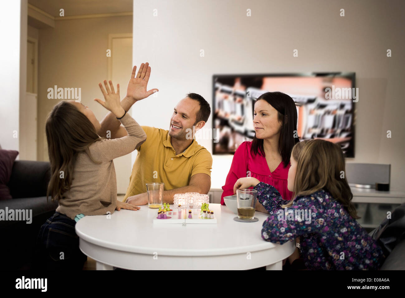 Father and daughter giving high-five while playing ludo at coffee table - Stock Image