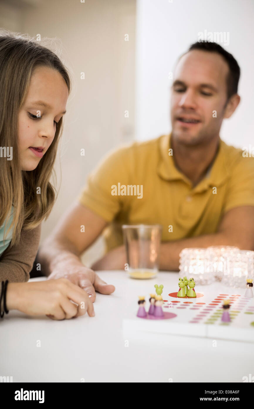 Father and daughter playing ludo at coffee table Stock Photo