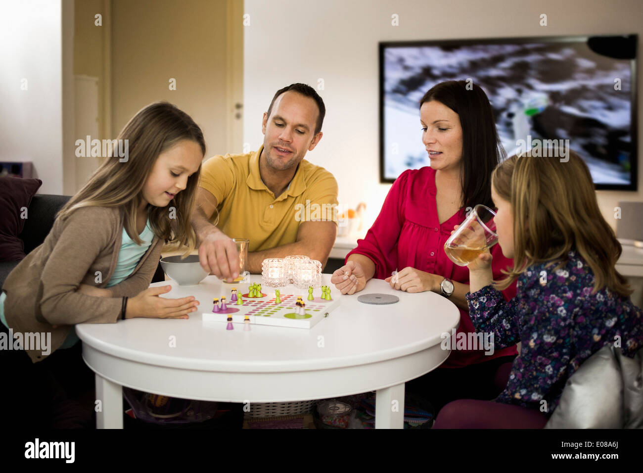 Family playing ludo in living room Stock Photo