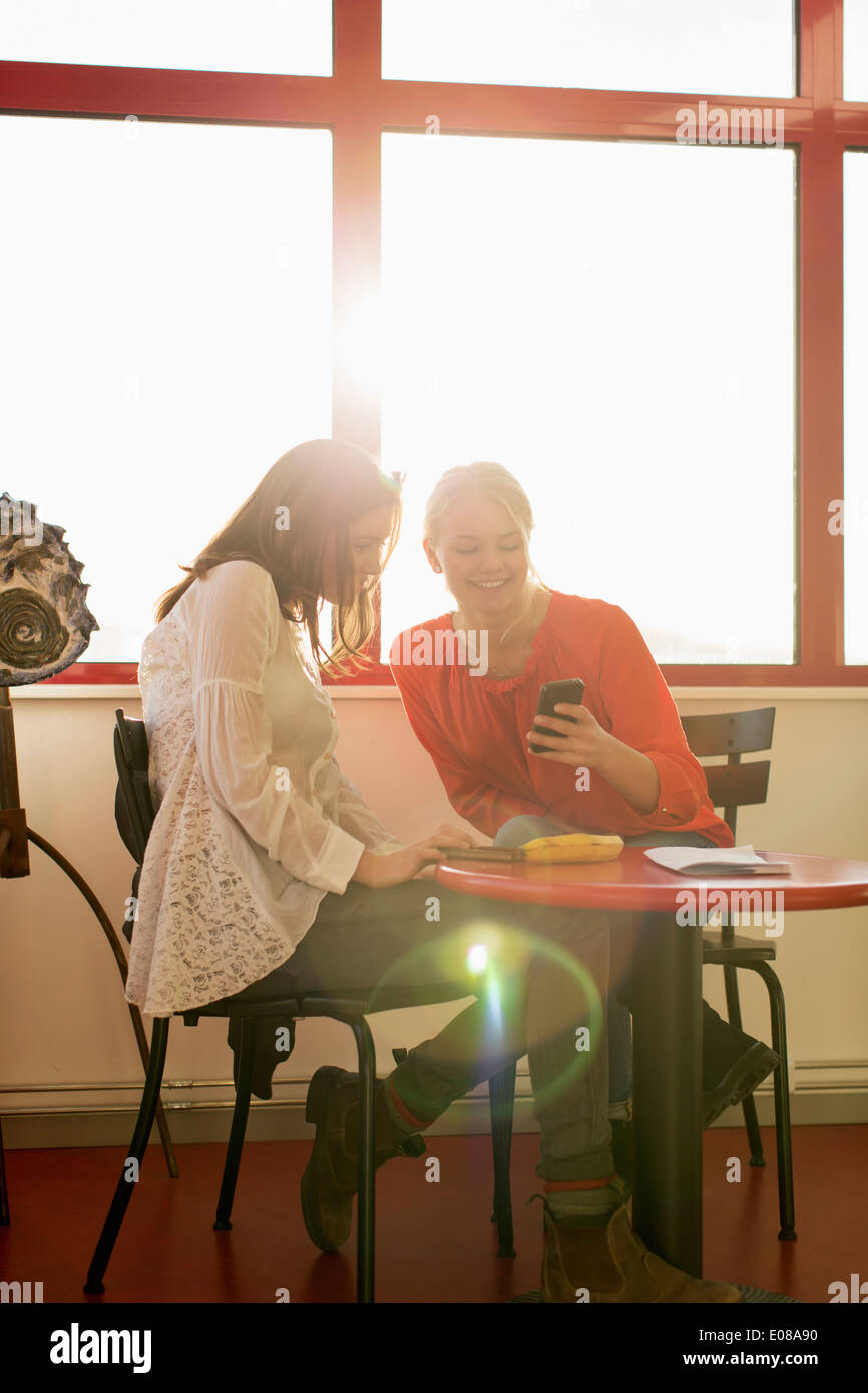 Happy teenage girls using mobile phone at school cafe Stock Photo