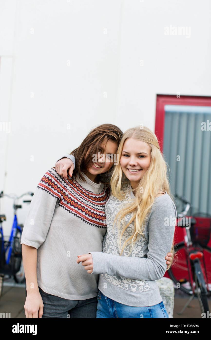 Portrait of happy teenage girls standing arm around on high school campus - Stock Image