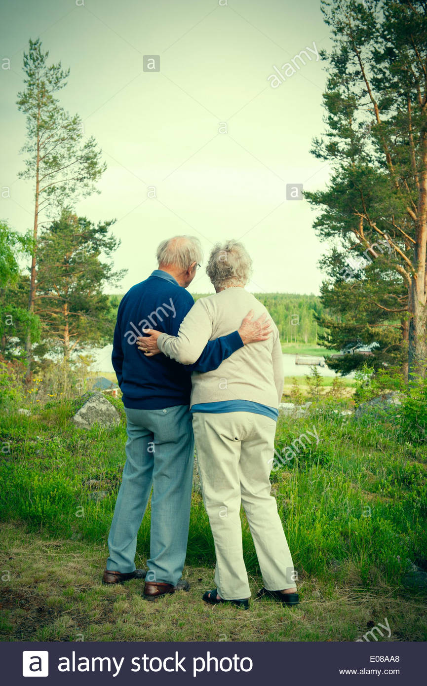 Full length rear view of senior couple looking at lake Stock Photo
