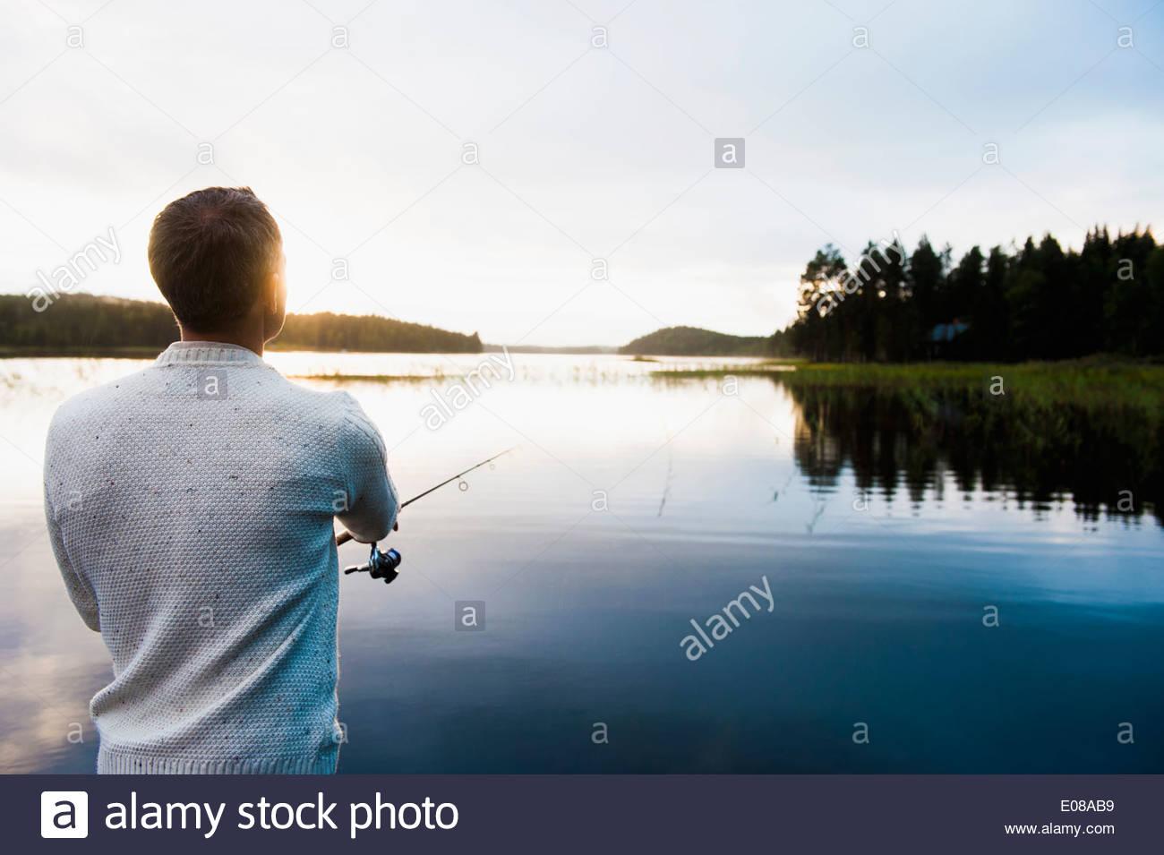 Rear view of man fishing at lake - Stock Image