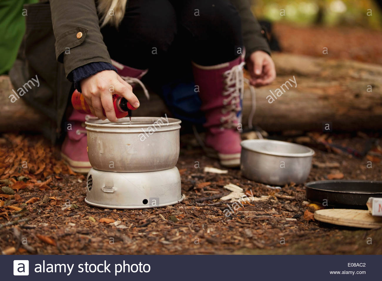 Low section of woman preparing food while camping in forest - Stock Image