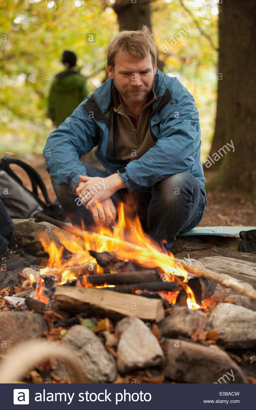 Mature man camping in forest - Stock Image
