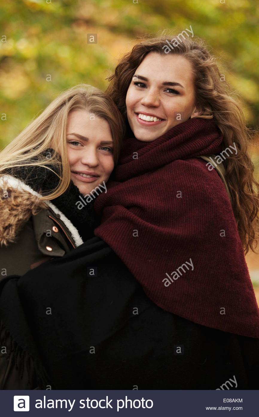 Portrait of sisters embracing outdoors - Stock Image