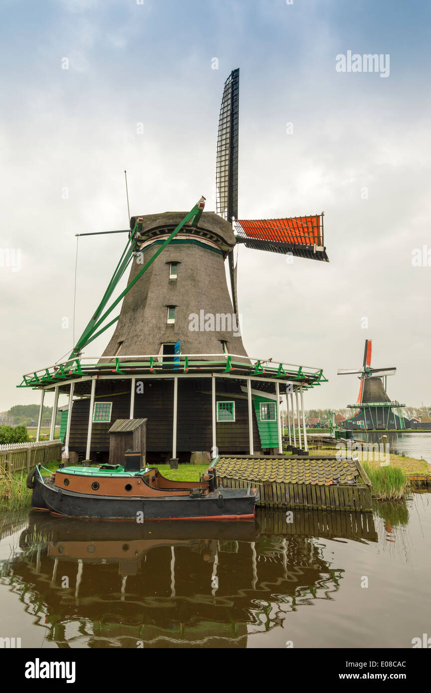 DUTCH WINDMILLS WITH ORANGE SAILS AND A BOAT ON THE CANAL AT ZAANSE SCHANS HOLLAND - Stock Image