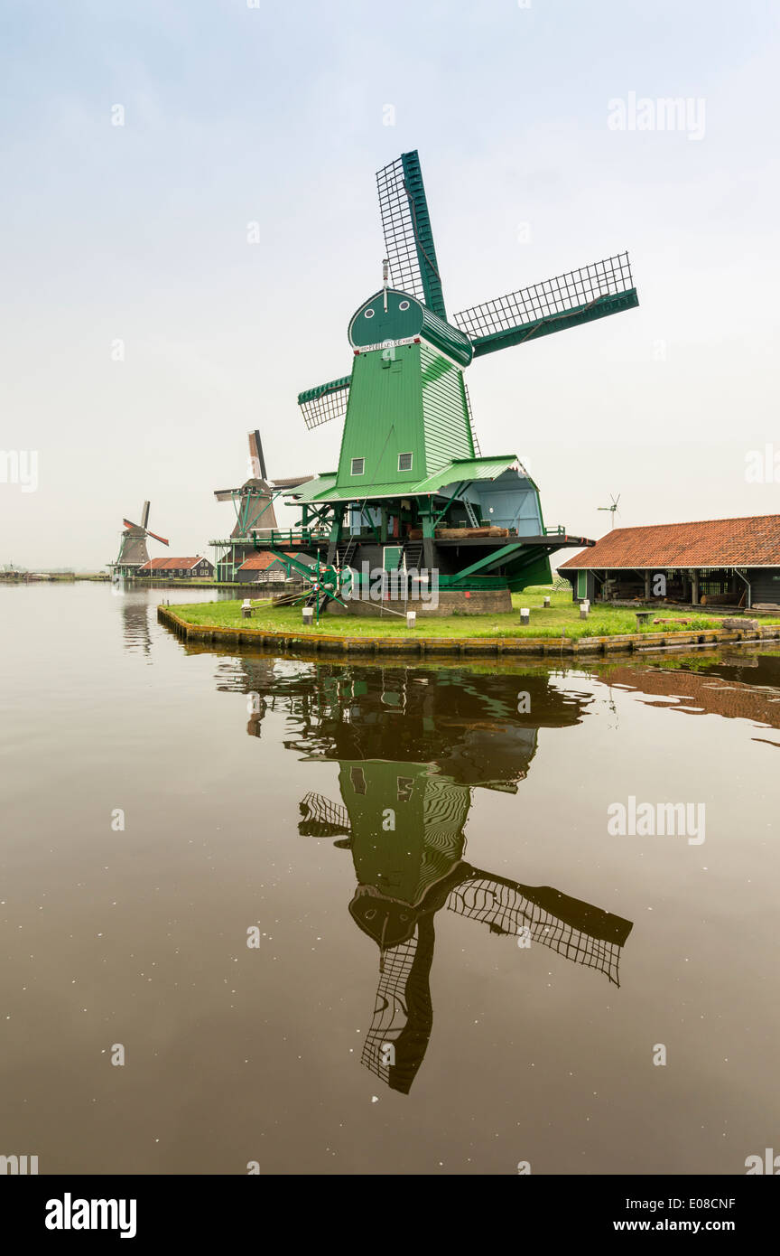 GREEN WINDMILL AND TWO OTHERS ON THE CANAL AT ZAANSE SCHANS  HOLLAND IN SPRINGTIME - Stock Image