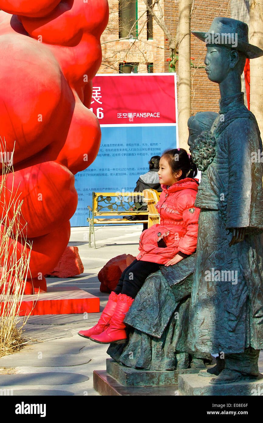 Young Chinese Girl Poses For A Photo With A Statue In The 798 Art Zone, Beijing, China. - Stock Image
