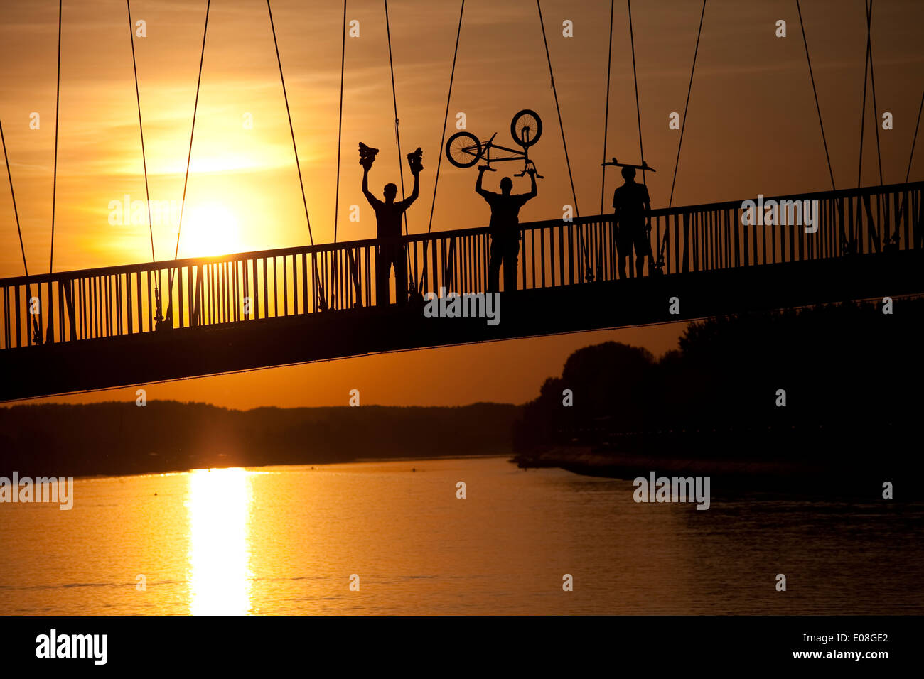 Young people with BMX cycle, inline skates and skateboard on footbridge, Osijek, Croatia - Stock Image