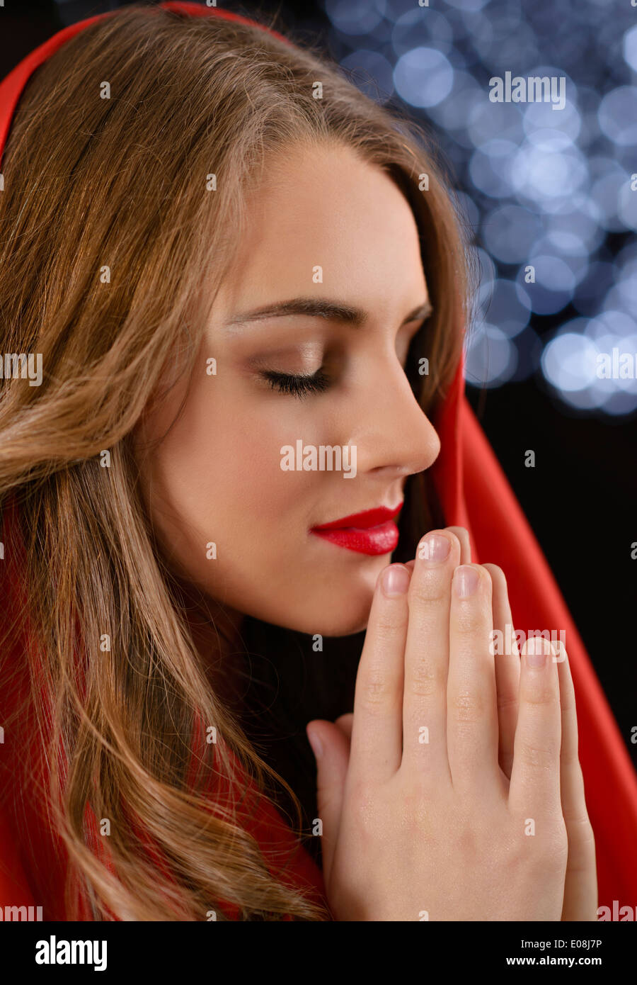Beautiful woman praying with blurred lights in background - Stock Image