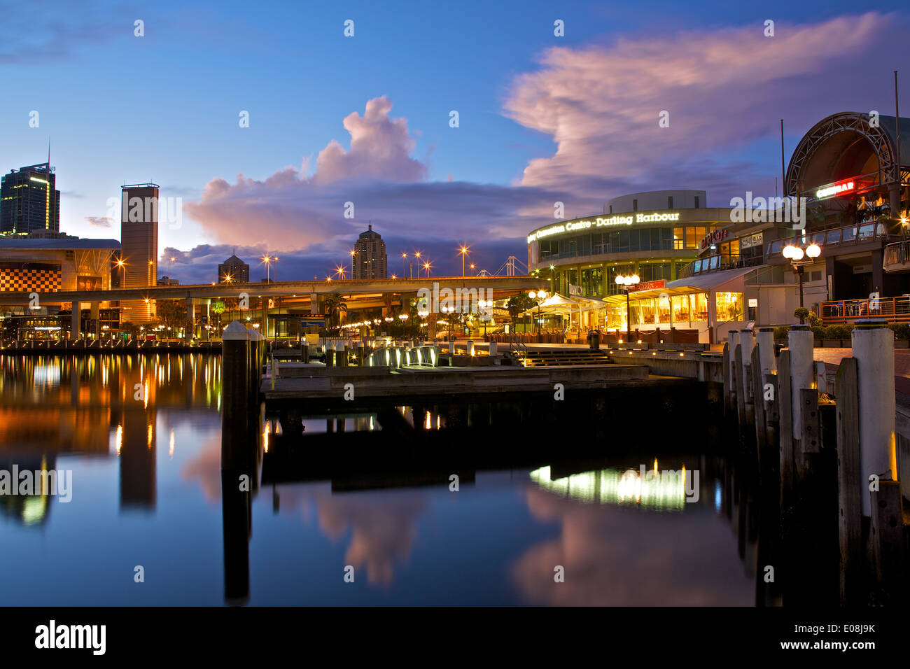 Dawn breaks over a stormy sky in Darling Harbour, Sydney, Australia. - Stock Image