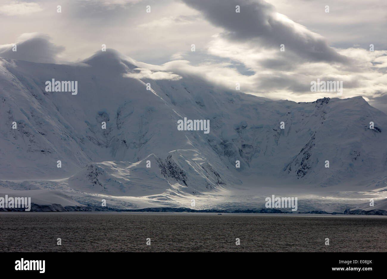 sunlight breaking through clouds on snow covered landscape of anvers island and neumayer channel Antarctica Stock Photo