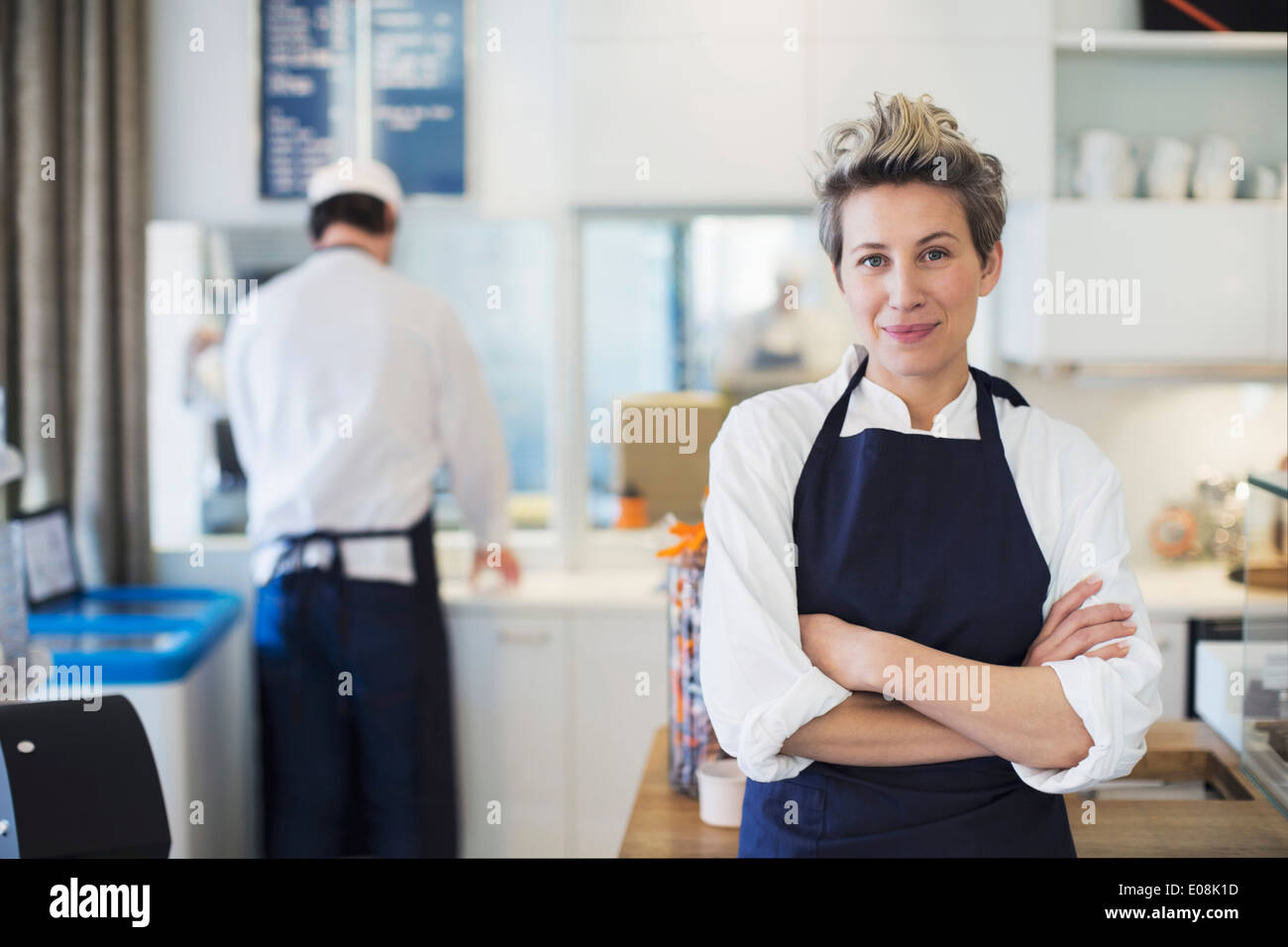 Portrait of confident female owner standing arms crossed in cafe - Stock Image