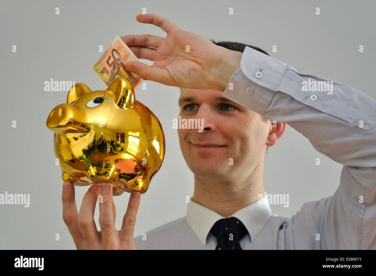 Illustration - A man puts a 50-euro-bill into a golden piggy bank in Germany, 27 February 2011. Photo: Berliner Stock Photo