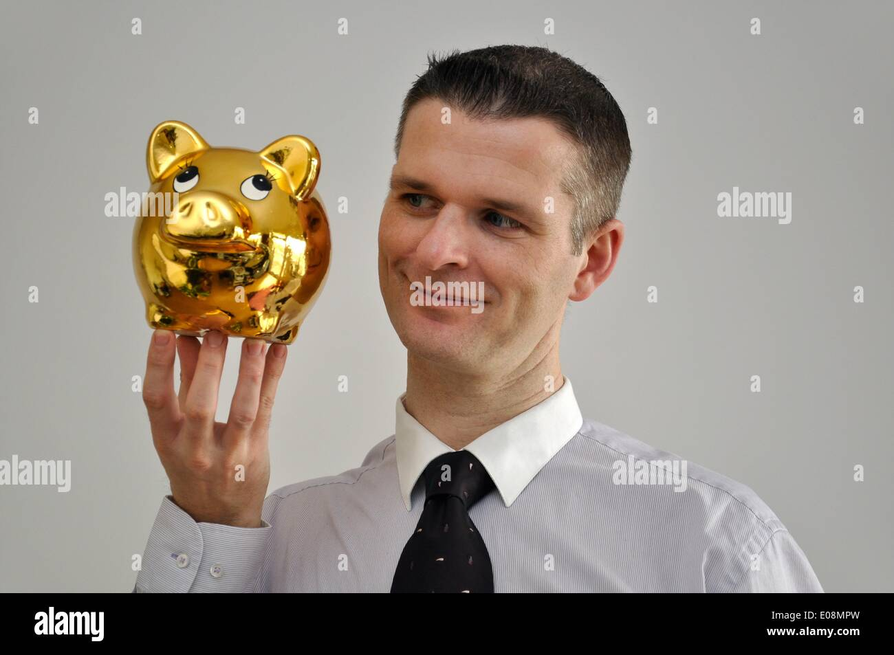 Illustration - A man holds a golden piggy bank in Germany, 27 February 2011. Photo: Berliner Verlag/Steinach - NO Stock Photo