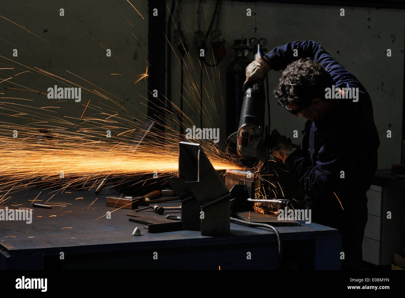 Factory worker using angle grinder to cut metal - Stock Image