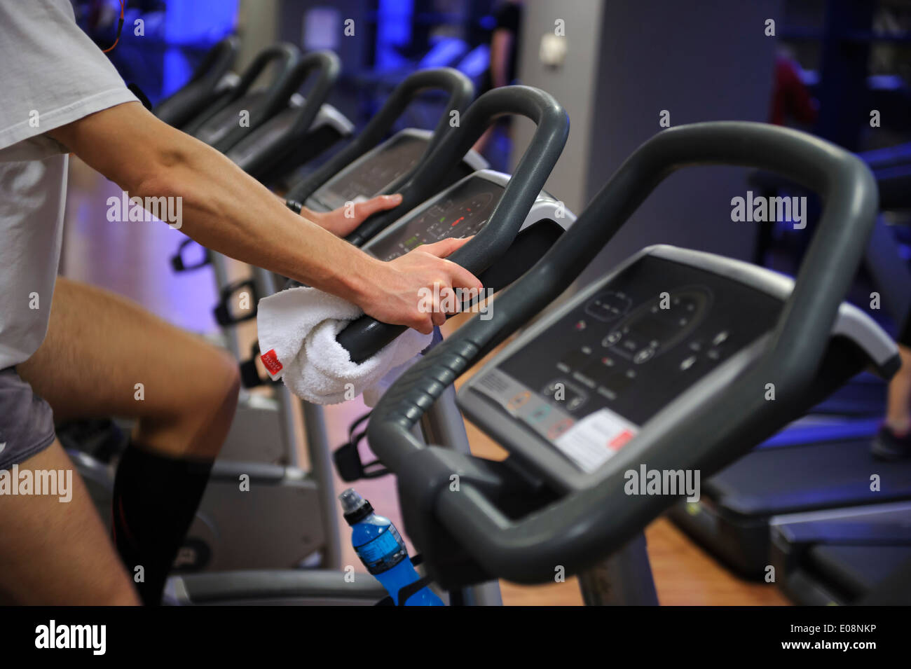 Person working out on exercise bike at the gym - Stock Image