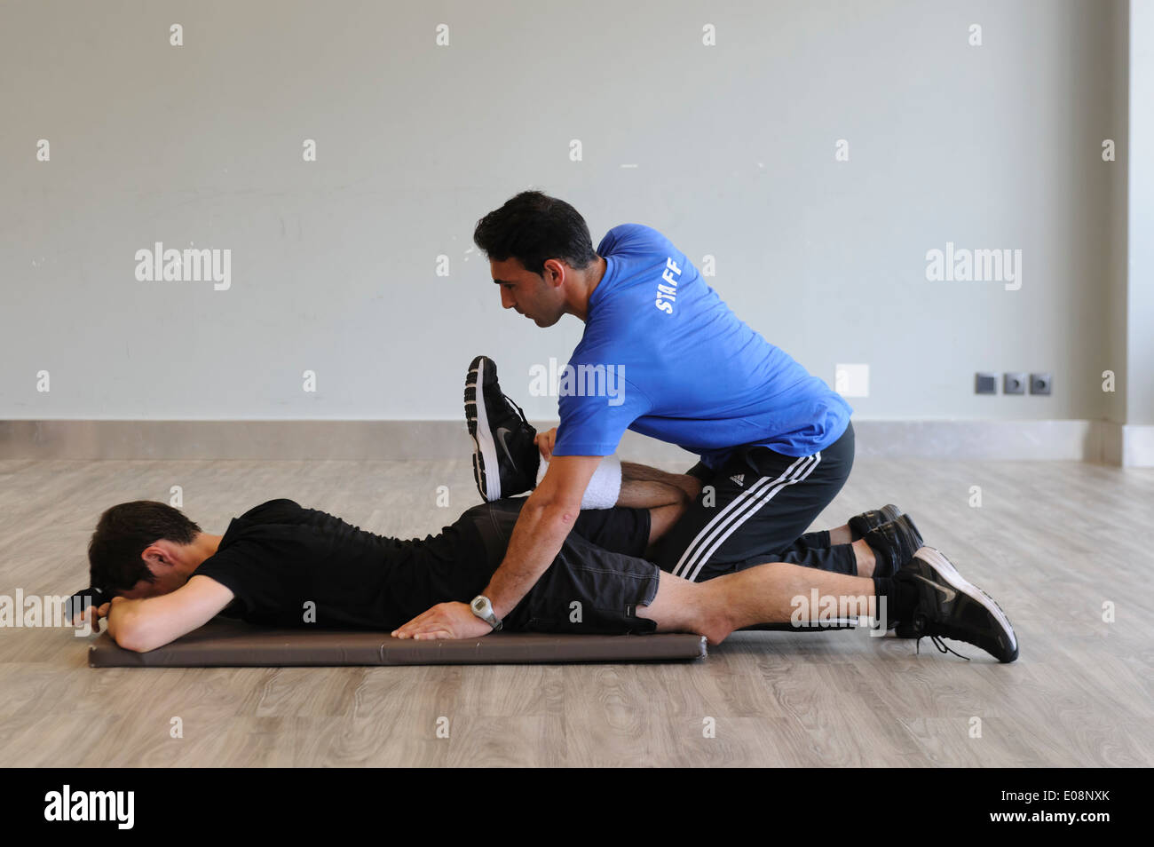 Personal trainer in the gym helping a client do stretching exercises - Stock Image