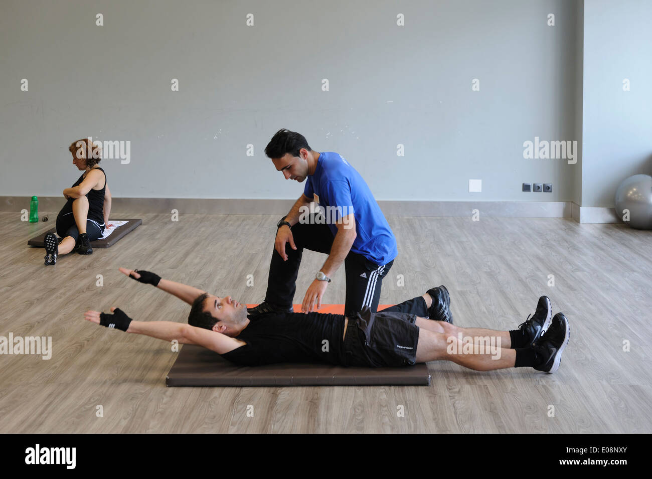 Personal trainer in the gym with a client - Stock Image