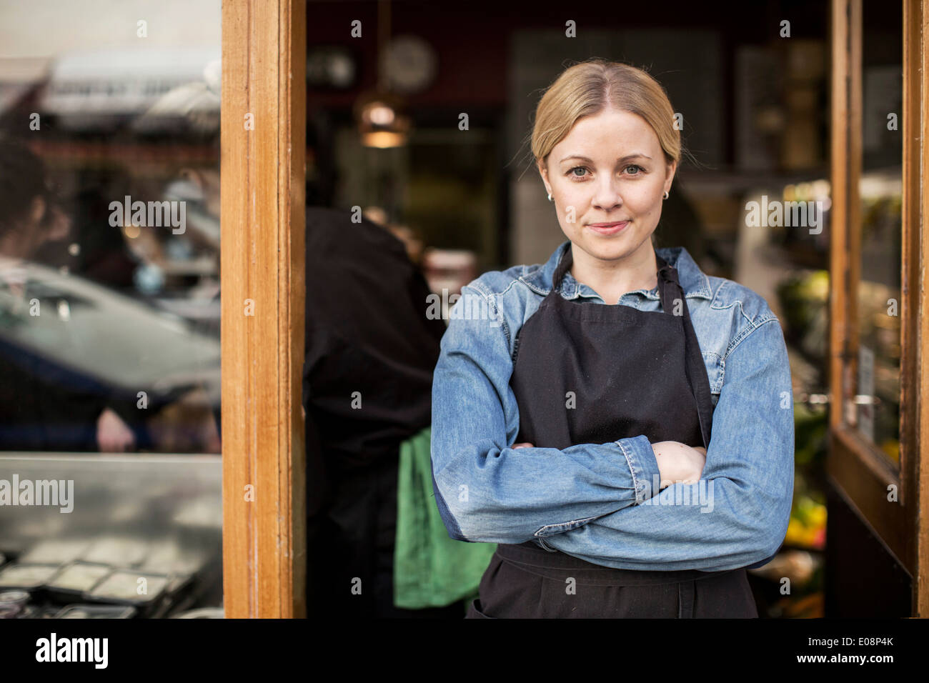 Portrait of confident saleswoman standing arms crossed at supermarket entrance - Stock Image