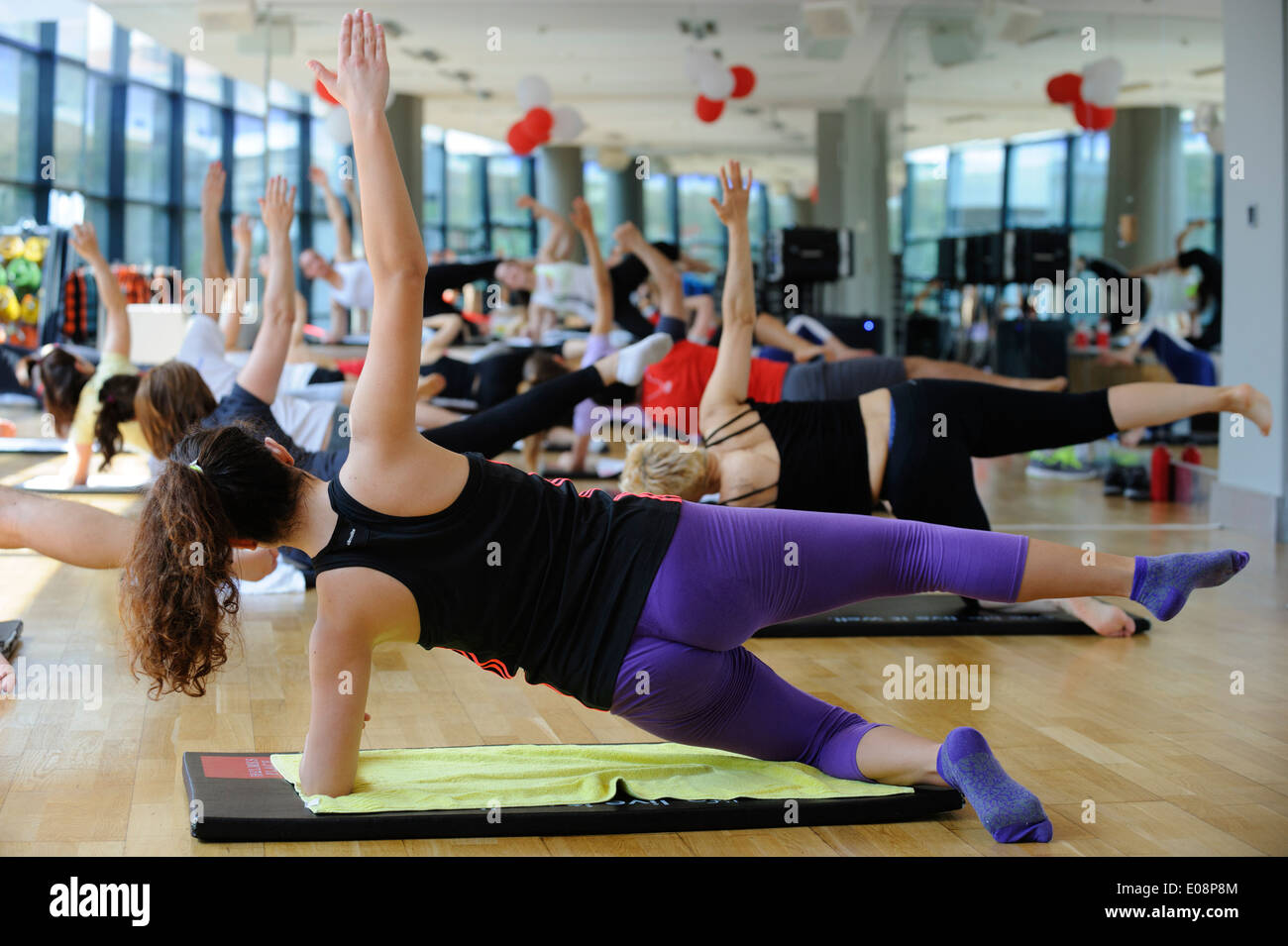Woman doing side plank during a fitness class at the gym - Stock Image